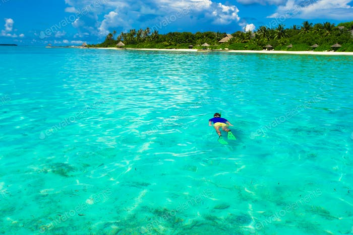 Young man snorkeling in clear tropical turquoise waters