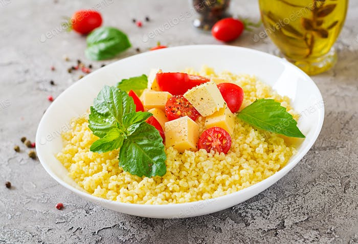Millet porridge with cheese, butter and basil in white bowl. Tasty food. Breakfast.