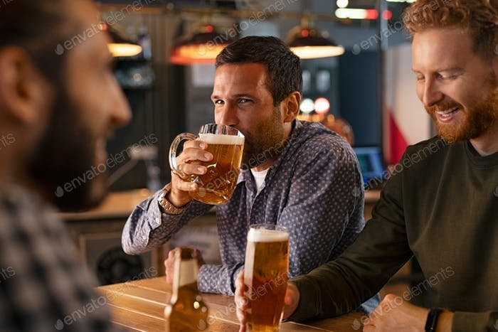 Man drinking draft beer with friends