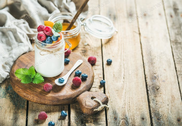 Glass jar of yogurt with berries, mint and honey