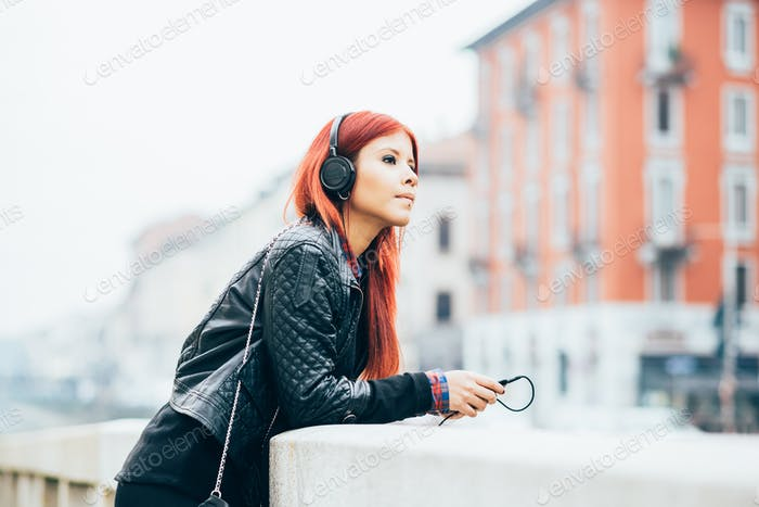 Knee figure of young beautiful hispanic redhead woman listening