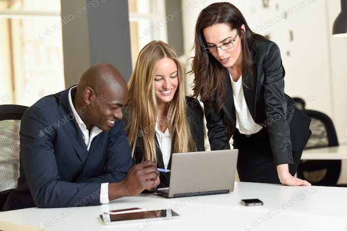 Multi-ethnic group of three businesspeople meeting in a modern o