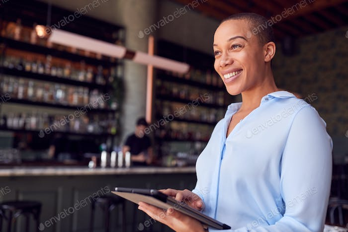 Confident Female Owner Of Restaurant Bar Standing By Counter Holding Digital Tablet