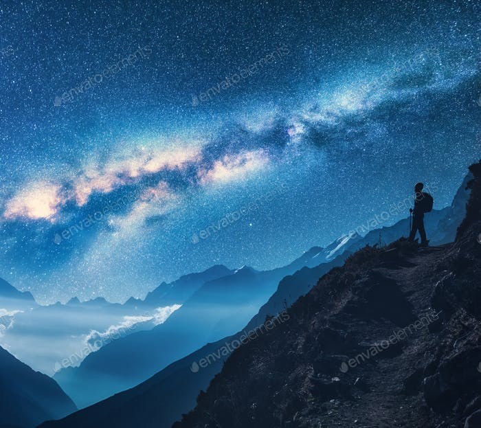 Milky Way and silhouette of standing woman on the mountain