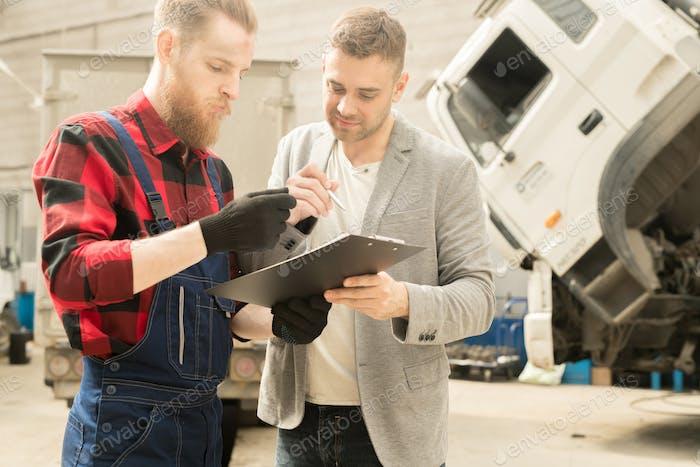 Mechaniker Blick auf die Checkliste mit dem Kunden