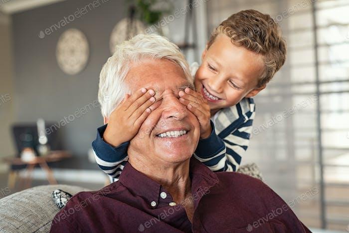 Playful little boy covering grandpa's eyes