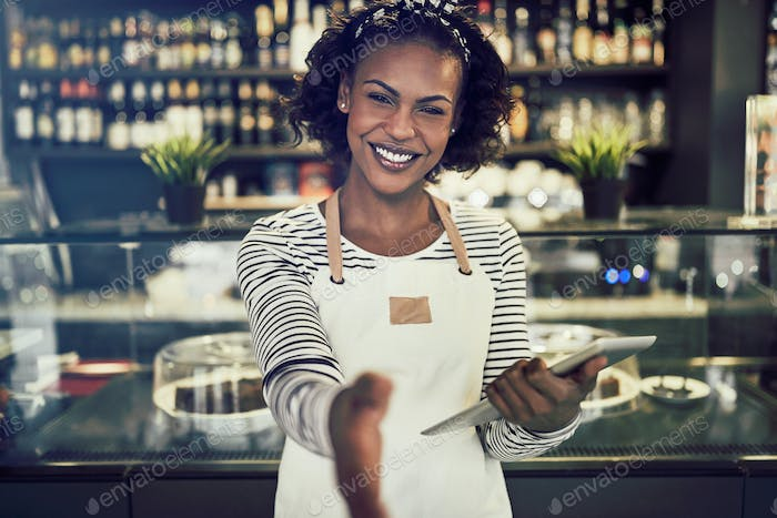 Smiling African hostess offering a handshake in her trendy cafe