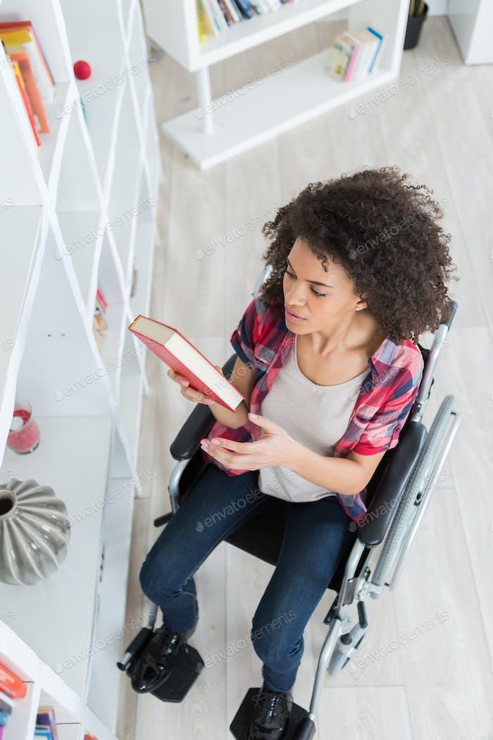 Behinderte Student in der Bibliothek Kommissionierung Buch an der Universität