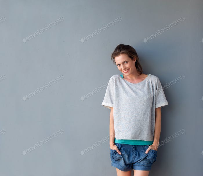 Beautiful mid adult woman smiling against gray background