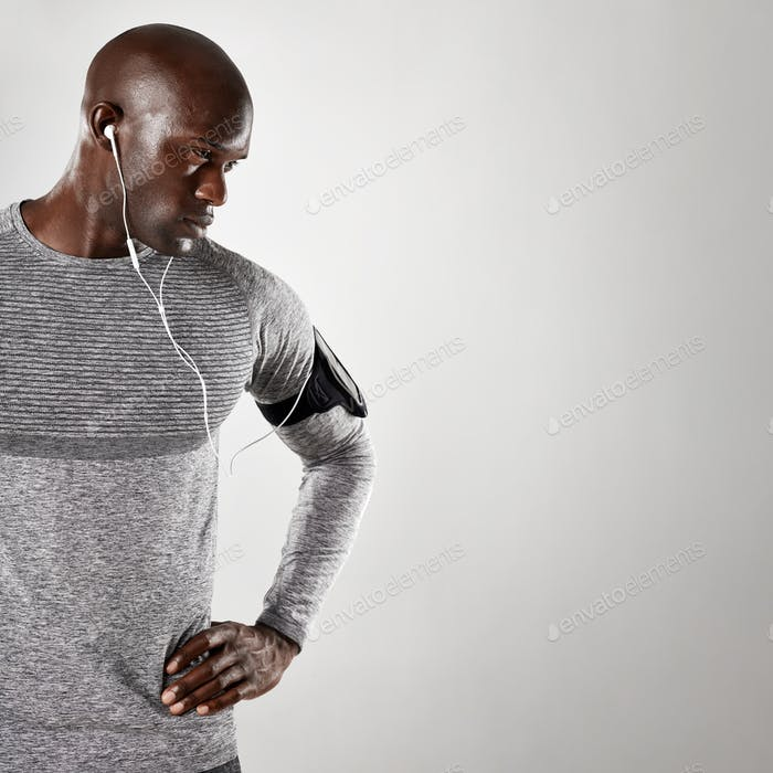 Tough young guy with earphones staring at copy space