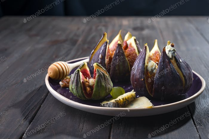 Figs appetizer with cheese, walnut and honey on ceramic plate
