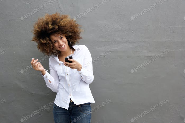 Attractive young woman smiling with earphones and smart phone