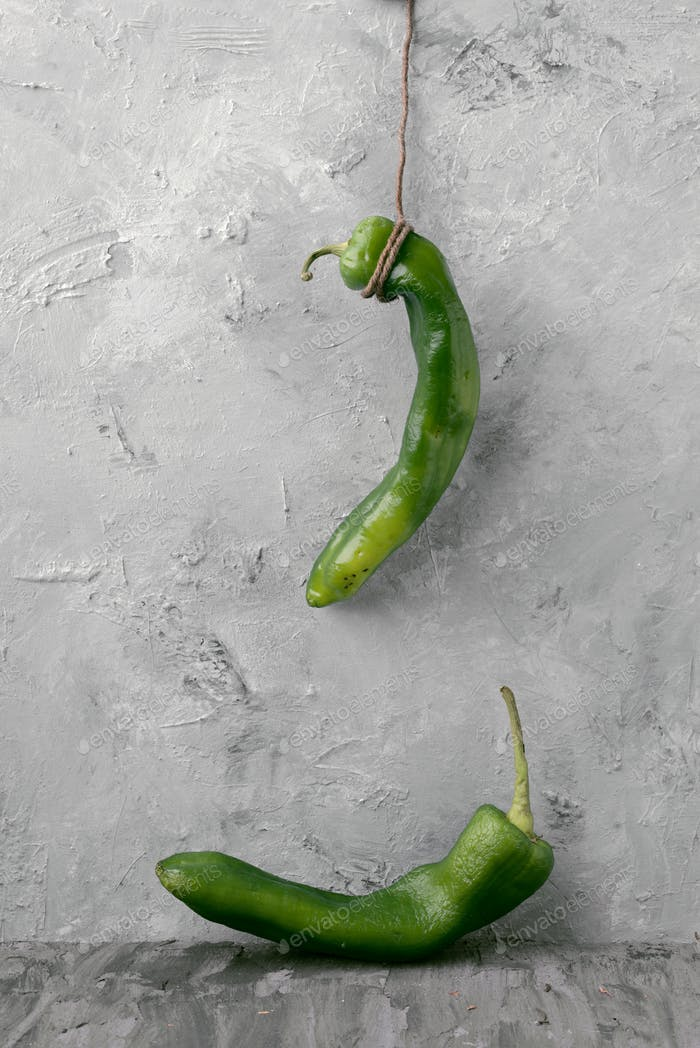 raw green peppers hanging in an arrangement, in front of gray marbling background