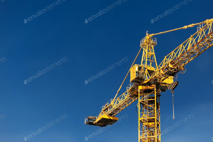 Construction crane tower in sun light beams on background of  blue sky