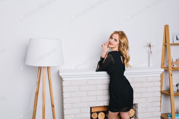 Attractive luxury blonde girl with golden wavy hair in white room with floor lamp and fake fireplace