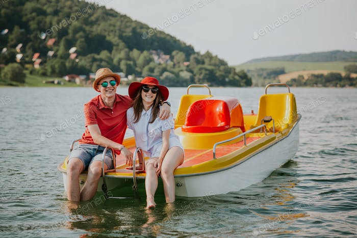 Front view of smiling young couple sitting on pedal boat.