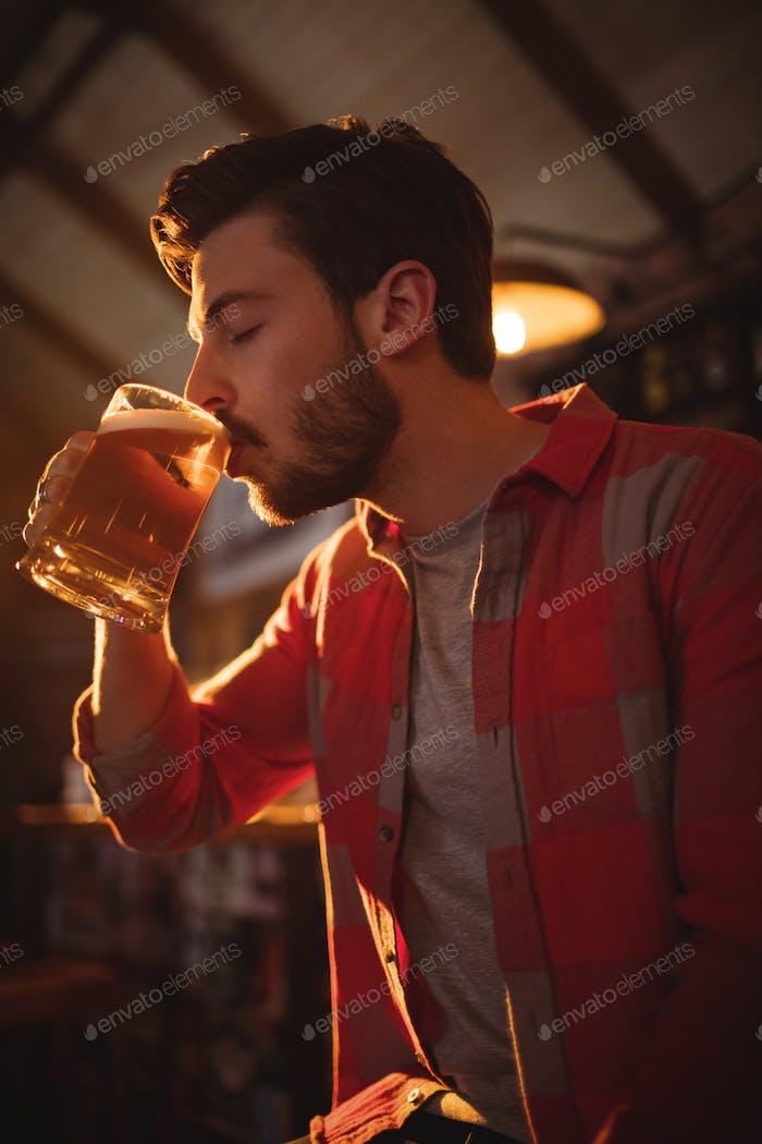 Young man having mug of beer