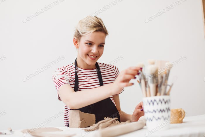 Girl in black apron and striped T-shirt sitting with clay happily selecting tools at pottery studio