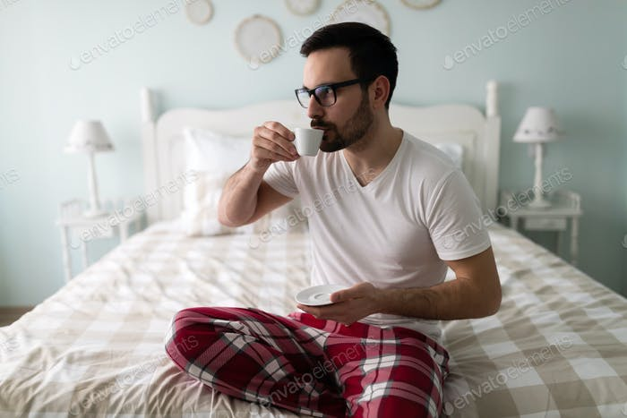 Young handsome man drinking coffee on his bed