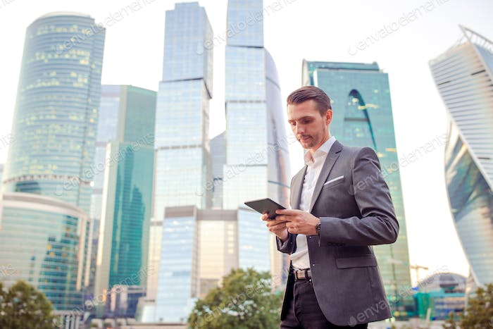 Young caucasian man holding smartphone for business work