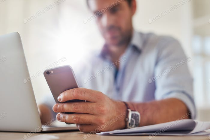 Young man using mobile phone while working on laptop