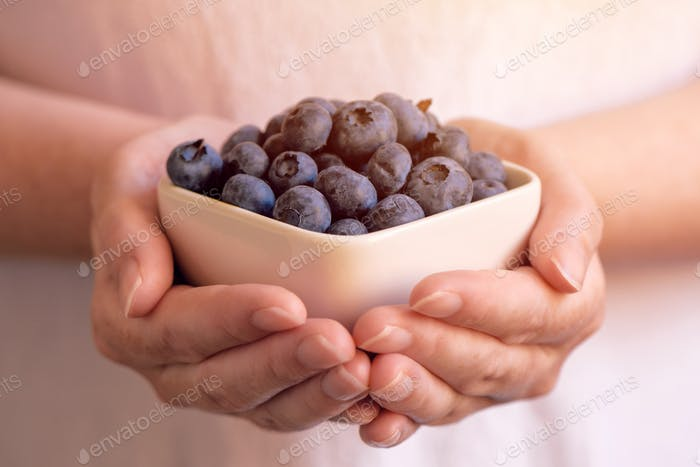 Woman offering a bowl of blueberries or bilberries