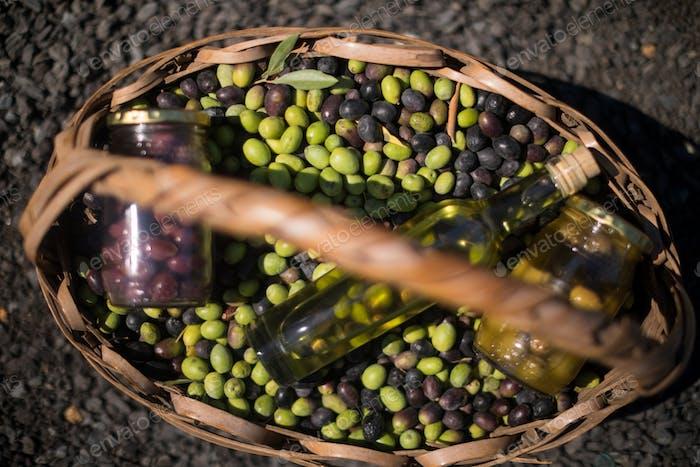 Close-up of olives, jar and olive oil bottle in basket