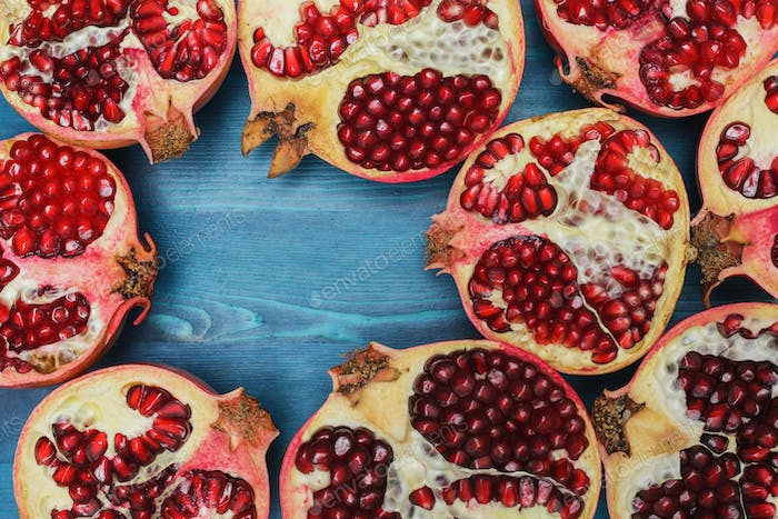 Cut in half pomegranate on a wooden blue surface