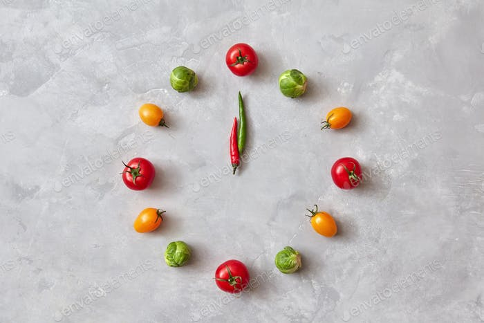 Moving colored vegetables make up a clock with moving arrows from chili pepper on a gray concrete
