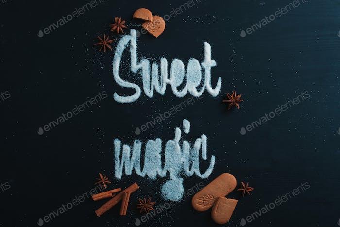 Worte Süße Magie mit Zucker gemacht. Kekse und Krümel auf einem dunklen Hintergrund. Lebensmittel-Typografie-Konzept
