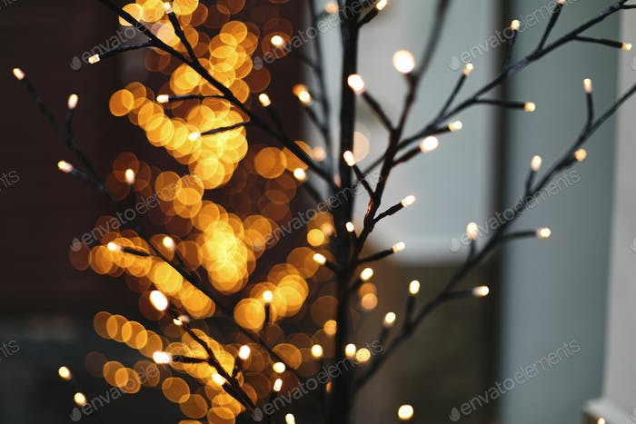 Tree trunk and branches in golden lights bokeh in evening. Holiday winter market