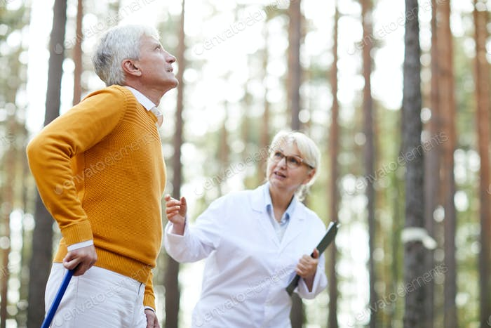 Doctor supporting senior patient at rehabilitation