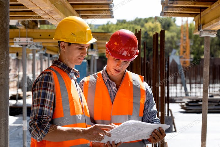 Structural engineer and architect dressed in shirts, orange work vests and helmets explore