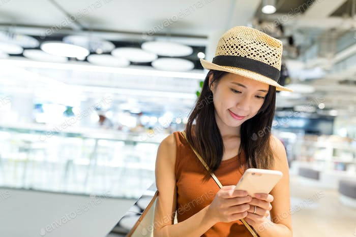 Woman use of cellphone in shopping mall