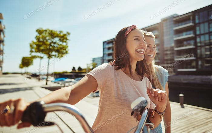 Best friends laughing while walking with a bicycle in summer