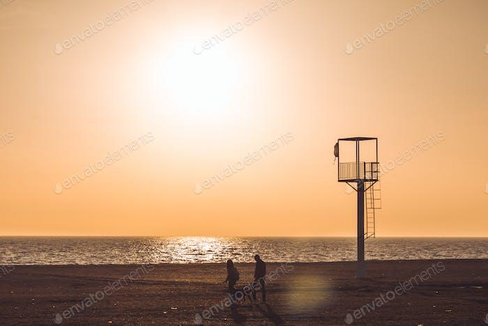 couple strolling along a desert beach at sunset