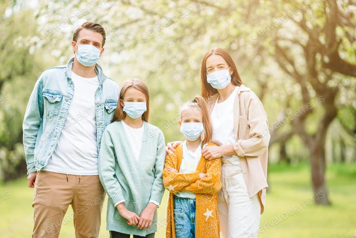 Adorable family in blooming cherry garden in masks