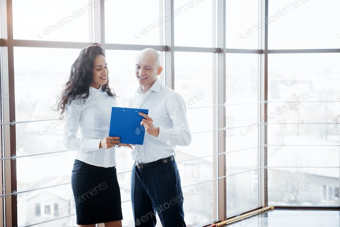 Businessman and woman studying a chart on the plate and paper documents
