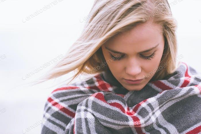 Cerca de una Mujer joven cubierta con manta en el Playa