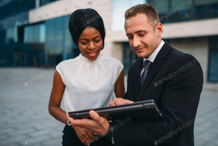 Business woman and businessman looks on laptop