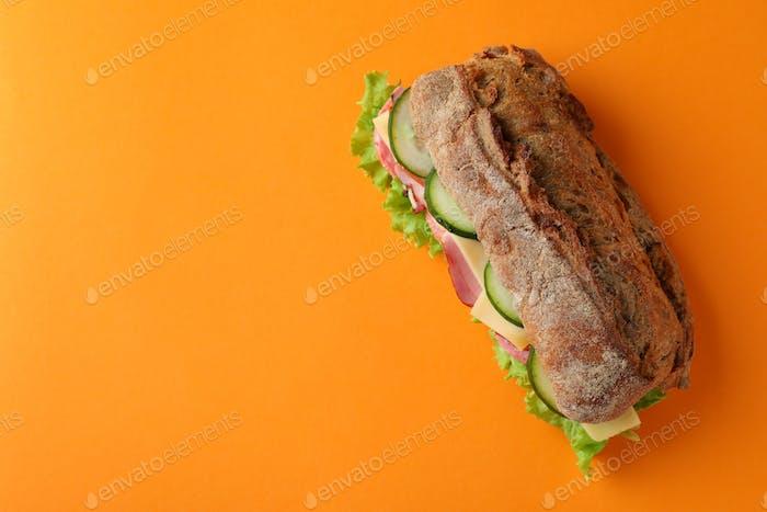 Sandwich of ciabatta bread on orange background