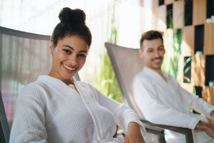 Portrait of young couple sitting and looking at camera in spar resort, relaxing