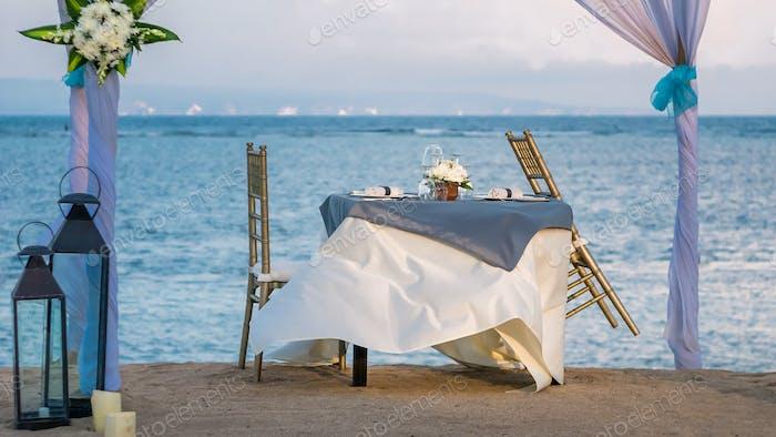 Cafe Table on a tropical sandy beach with sea on background, Nusa Dua, Bali