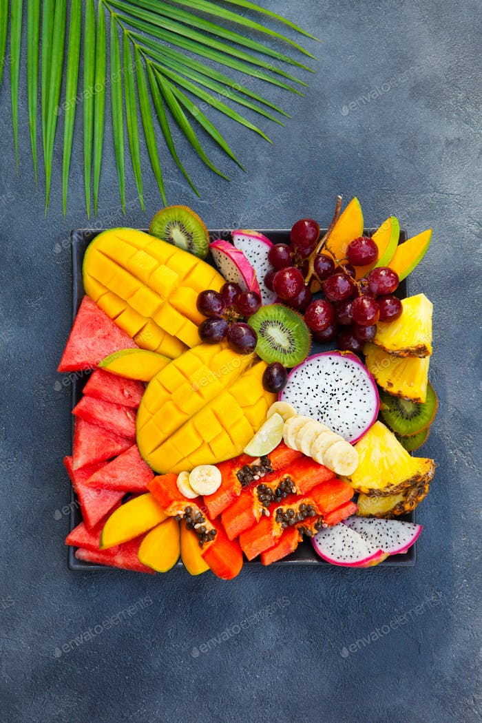 Tropical fruits assortment on a plate. Grey background. Top view.