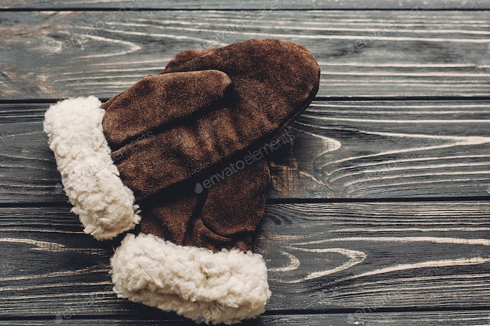 warm cozy gloves on rustic background top view