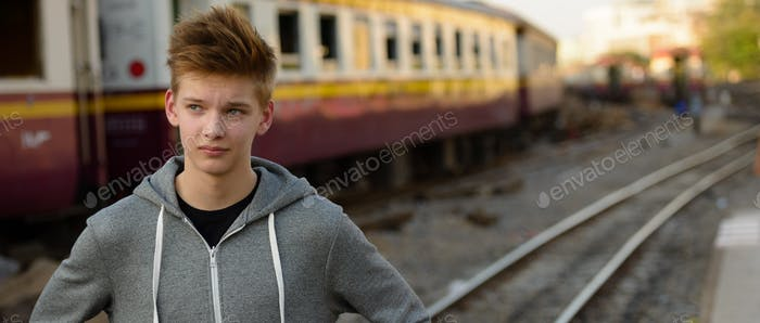 Young handsome teenage boy at the railway train station