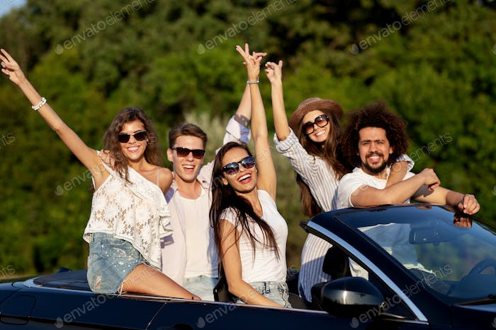 Happy beautiful young dark-haired girls and guys in sunglasses smile in a black cabriolet on the