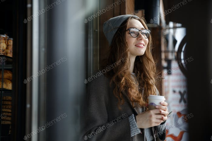 Happy attractive young woman thinking and drinking coffee outdoors