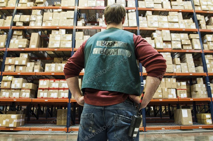 Warehouse worker checking inventory on the storage racks in a distribution warehouse.