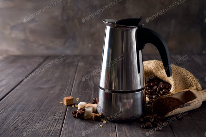 on the background of a bag of coffee and sugar grains on a dark wooden background, copy space